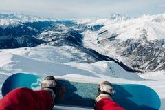 O Snowboarder com snowboard sentado na montanha foto de stock royalty free
