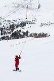O snowboarder da menina aumenta acima no esqui-reboque em cumes franceses Imagens de Stock Royalty Free
