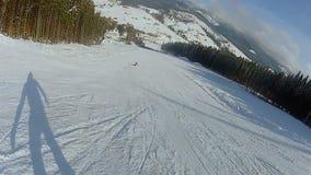 O snowboarder do estilo livre que faz truques durante o passeio esquia para baixo trilha na inclinação de montanha vídeos de arquivo
