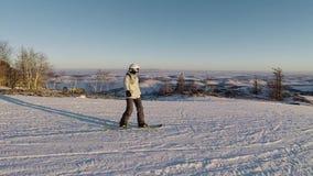 O Snowboarder está deslizando para baixo na inclinação de montanha na estância de esqui no dia ensolarado da geada A menina no eq vídeos de arquivo
