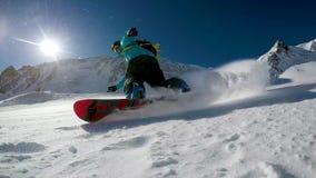 O Snowboarder faz a neve espirrar na inclinação no dia ensolarado filme