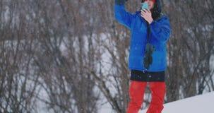 O Snowboarder joga uma bola de neve na posição da câmera na inclinação do esqui vídeos de arquivo