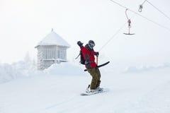 O Snowboarder levanta-se acima a montanha em céu-levanta Foto de Stock Royalty Free