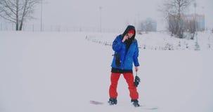 O snowboarder masculino em um casaco azul é transmissão em direto de seu smartphone na estância de esqui video estoque