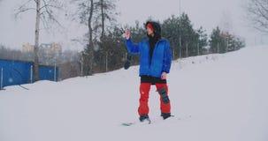 O snowboarder masculino em um casaco azul ? transmiss?o em direto de seu smartphone na est?ncia de esqui video estoque