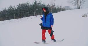 O snowboarder masculino monta a placa no esqui à inclinação da neve e mensagens da escrita ao smartphone a seus amigos video estoque