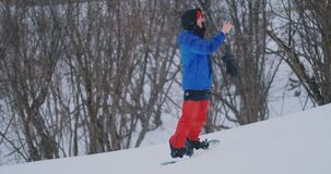 O snowboarder masculino monta a placa no esqui ? inclina??o da neve e mensagens da escrita ao smartphone a seus amigos filme