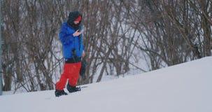 O snowboarder masculino monta a placa no esqui ? inclina??o da neve e mensagens da escrita ao smartphone a seus amigos video estoque