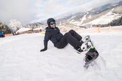 O Snowboarder no monte abotoa a asseguração antes do passeio no monte da neve imagem de stock