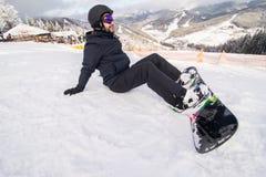 O Snowboarder no monte abotoa a asseguração antes do passeio no monte da neve fotos de stock