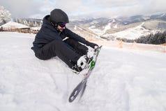 O Snowboarder no monte abotoa a asseguração antes do passeio no monte da neve fotografia de stock