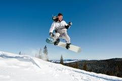 O Snowboarder que salta através do ar Fotografia de Stock Royalty Free