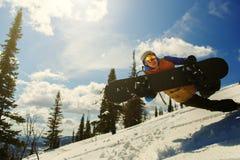 O Snowboarder que salta através do ar com snowbord Imagens de Stock Royalty Free