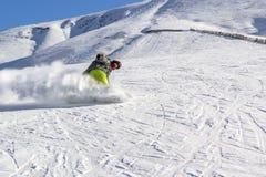O Snowboarder rola rapidamente para baixo em uma nuvem da poeira da neve contra um céu azul em um dia ensolarado imagem de stock