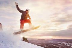 O Snowboarder salta contra o céu do por do sol Foto de Stock