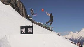 O Snowboarder salta da bola do lance do trampolim na cesta do basquetebol audiências video estoque