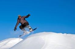 O Snowboarder salta no ar, vôo da neve fotografia de stock royalty free