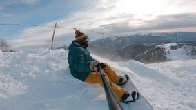 O Snowboarder senta-se altamente nas montanhas na borda da inclina??o e olha-se na dist?ncia vídeos de arquivo