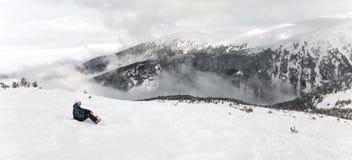 O Snowboarder senta-se com o snowboard nas mãos senta-se na rocha grande no contexto das montanhas Bansko, Bulgária foto de stock royalty free