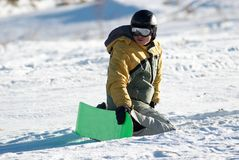 O Snowboarder senta-se na inclinação Imagens de Stock Royalty Free