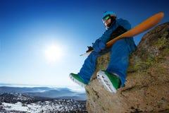O Snowboarder senta-se no contexto do céu azul nas montanhas Fotos de Stock