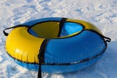 O snowtube amarelo e azul está na neve branca Fotografia de Stock