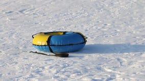 O snowtube amarelo e azul está na neve branca no dia de inverno filme