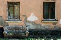 o sofá abandonado de couro velho na rua na fachada da casa destruída, as plantas brotou através do estofamento do fotografia de stock