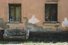 o sofá abandonado de couro velho na rua na fachada da casa destruída, as plantas brotou através do estofamento do imagens de stock royalty free