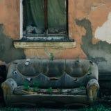 o sofá abandonado de couro velho na rua na fachada da casa destruída com janela, as plantas brotou com imagens de stock