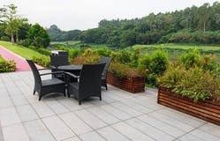 O sofá e a tabela do Rattan ajustaram-se em um jardim fotos de stock royalty free