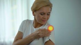O sofrimento fêmea da dor na articulação do úmero, ponto indica a inflamação filme