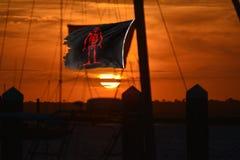 O sol ajusta-se com uma bandeira de pirata que acena defiantly na brisa dura imagem de stock royalty free