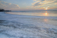 O sol ajustado sobre o lago congelado Foto de Stock Royalty Free