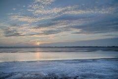 O sol ajustado sobre o lago congelado Imagens de Stock
