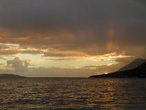 O sol atrás das montanhas e abaixo das nuvens foto de stock