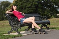 O sol bonito da mulher do skater do rolo tans no parque fotografia de stock