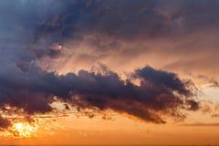 O sol brilha através das nuvens no por do sol imagens de stock