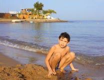 O sol considerável do Preteen bronzeou-se o menino no amor do whrite da praia do Mar Vermelho imagens de stock