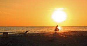 O sol da praia ajustou-se com o homem que move-se sobre com sacos fotos de stock