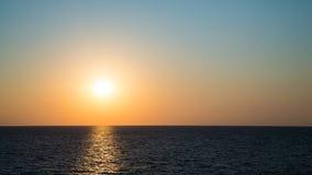 O sol de ajuste e o céu claro acima das águas do Mar Negro imagens de stock