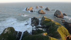 O sol de ajuste ilumina pedregulhos e ondas do ponto da pepita filme