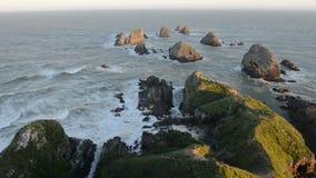 O sol de ajuste ilumina pedregulhos e ondas do ponto da pepita video estoque