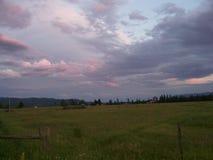 O sol de ajuste sobre um prado gramíneo cercado por florestas e por montanhas Imagens de Stock