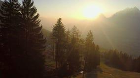 O sol dourado fantástico irradia o brilho nas montanhas, atmosfera mágica, pouca vila video estoque