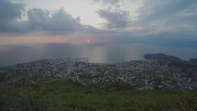 O sol dourado que afoga-se no mar no por do sol, cidade ilumina o timelapse, nivelando o cloudscape video estoque