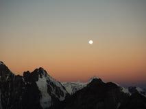 O sol levanta-se acima das nuvens do mar e do ouro Picos de montanha alvorecer Lua Fotos de Stock Royalty Free