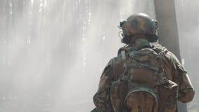 O soldado do exército dos EUA corre através da floresta smoggy durante a batalha filme