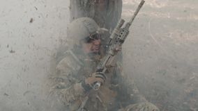 O soldado em um pânico esconde atrás de uma árvore durante a luta na floresta video estoque