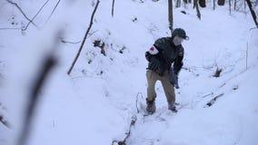 O soldado esgotado anda através de uma floresta nevado filme